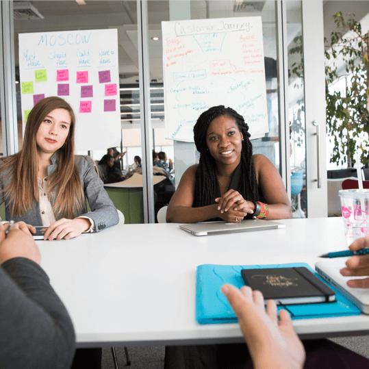 Zwei Frauen und zwei weitere Personen in einer Besprechung in einem Konferenzraum oder Büro.