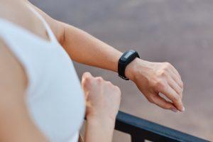 Frau prüft Fitnesstracker, Konzept Bewegung bei adipösen Brustkrebs-Patientinnen